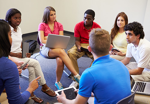 Seven students sit in a circle to engage in conversation