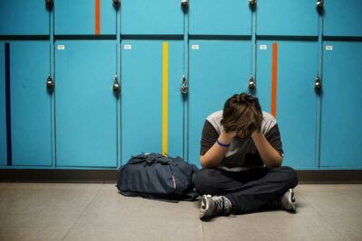Child sitting on the ground, hands on face upset in a school hallway.