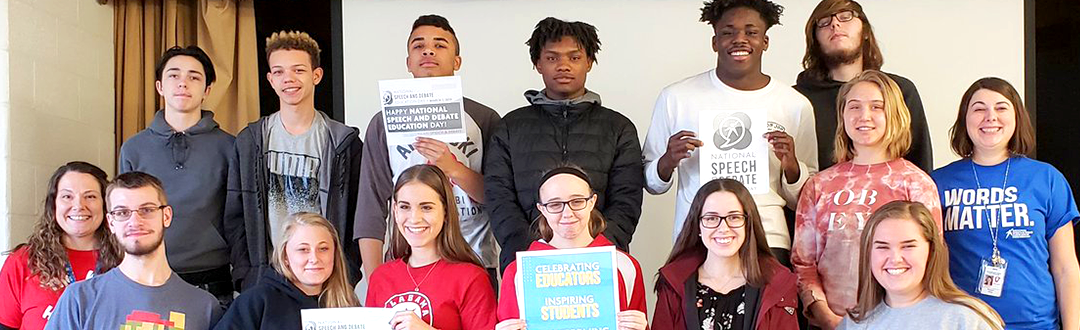 Students posing for a photo holding signs